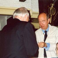 Prof.ir. C.M. van den Bleek overhandigt een afscheidscadeau aan Dr. A.J.H. Nollet. De administrateur van het Hoogewerff-Fonds, mevrouw C.M. van der Loo-Vreeburg, applaudiseert.